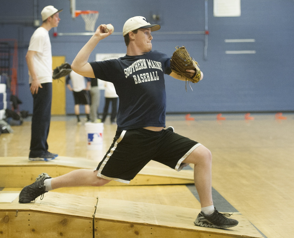 Westbrook's Ethan Nash, a senior pitcher, throws off a fabricated mound in the gym on Monday, as schools across the state started preparing for the spring sports season.