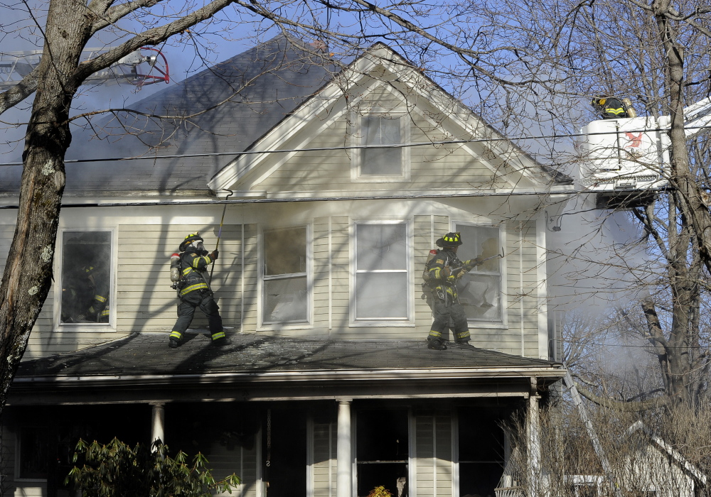 Portland firefighters battle a house fire at 38 Columbia Road in Portland on Monday. Fire investigators say the electrical system is likely the cause.