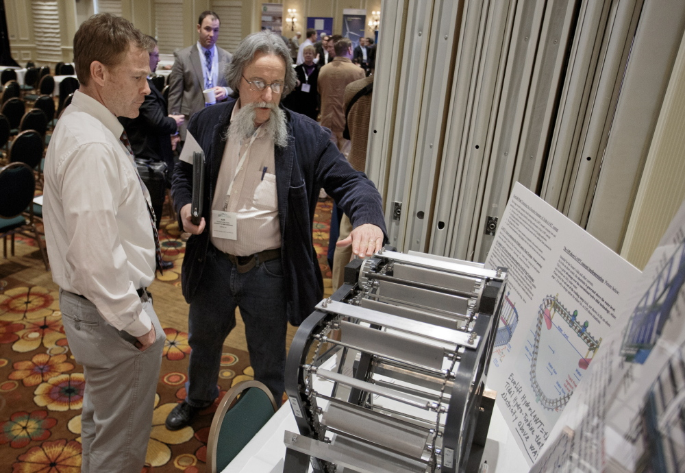 Warren Schmelzer, left, of EverLift Inc. and Ken Baldwin of the University of New Hampshire discuss one of EverLift's new turbine designs Tuesday at a wind energy summit.