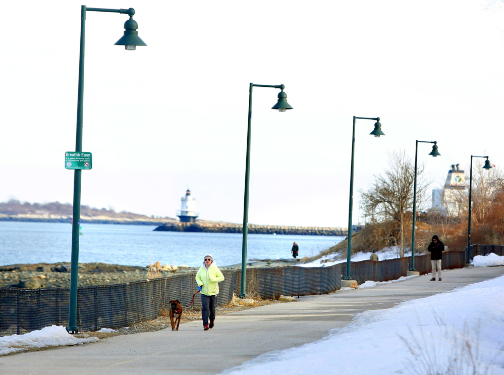 Christina Tavares of South Portland and her dog Hank run March 17 along the Eastern Promenade Trail. In the summer, there are guided tours of the lighthouse in the background, Spring Point Ledge Lighthouse in South Portland.