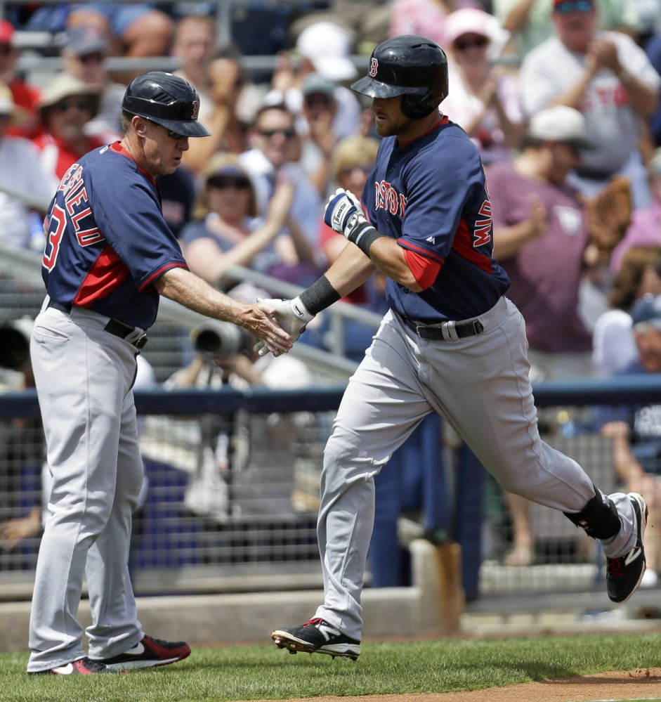 Boston Red Sox's Will Middlebrooks, right, is greeted by Boston Red Sox third base coach Brian Butterfield as he rounds third base on his solo home run in the third inning of an exhibition baseball game against the Tampa Bay Rays in Port Charlotte, Fla., Tuesday, March 25, 2014. The Red Sox won 4-2.