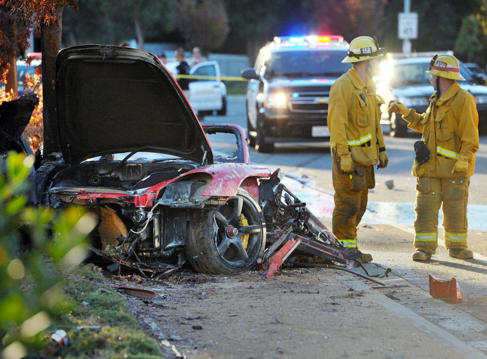 Firefighters work next to the wreckage of a Porsche that crashed into a light pole killing actor Paul Walker and Roger Rodas in Valencia, Calif. Crash investigators have determined that the Porsche was traveling approximately 90 mph at the time, according to someone who has seen the report.