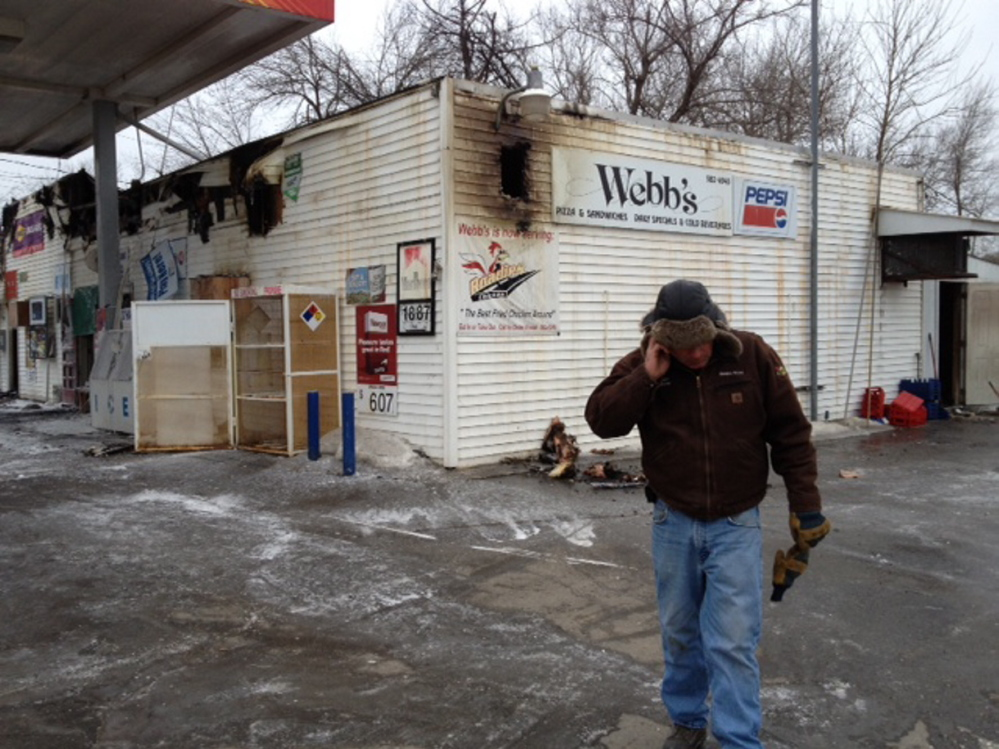 Staff photo by Andy Molloy Webb's Store owner Dan Kilmer speaks on the phone Wednesday morning after a fire destroyed the business overnight.