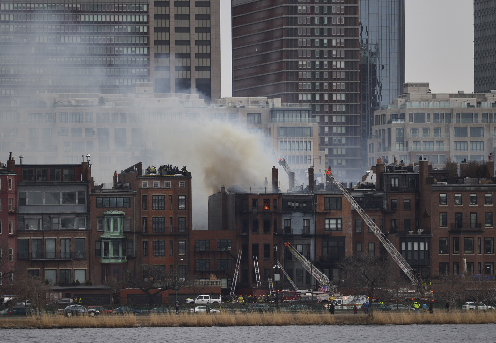 Smoke pours from the burning Boston brownstone, seen from Cambridge, Mass., as firefighters respond.