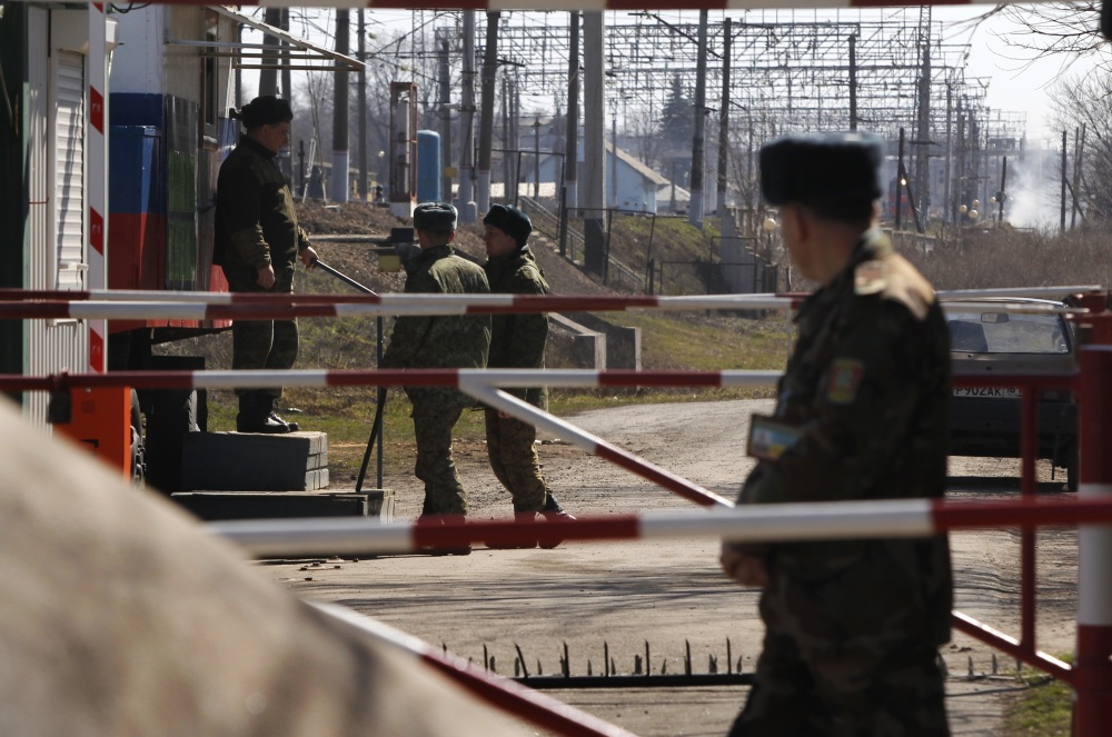 A Ukrainian border guard, right, and Russian border guards, left, are seen at the border crossing in Vyselki – a village that has been split between Ukraine and Russia since 1991.