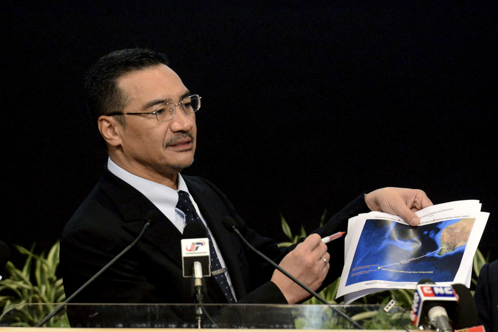 The Associated Press Malaysia's Defense Minister and acting Transport Minister Hishammuddin Hussein shows a printout of the latest satellite image of objects that might be from the missing Malaysia Airlines plane, on March 26, 2014.