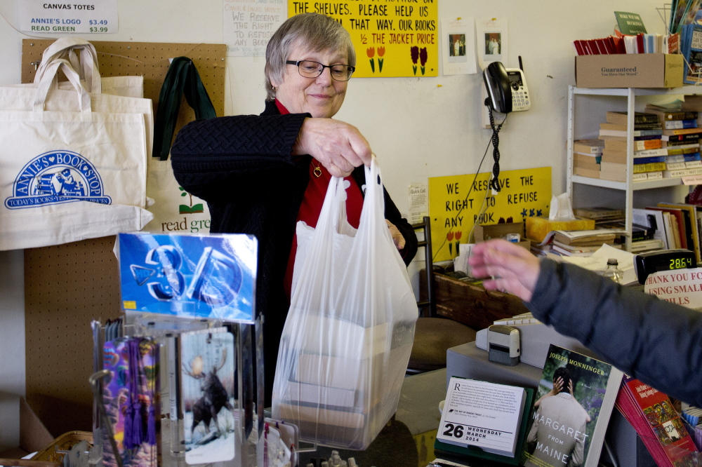 Alice Moisen, owner of the soon-to-be-closed Annie's Book Stop in Portland, hands a bag of half-price books to a customer on Wednesday.