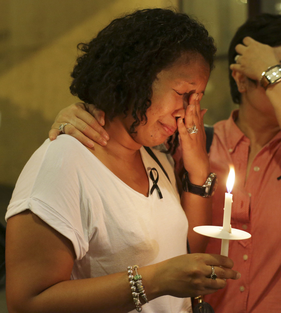 A woman wipes tears at a ceremony in memory of passengers on Malaysia Airlines Flight MH370 in Kuala Lumpur on Thursday.
