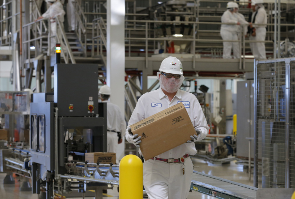 An associate carries a box of Snickers as production begins at the Mars Chocolate North America Topeka Plant on Thursday.
