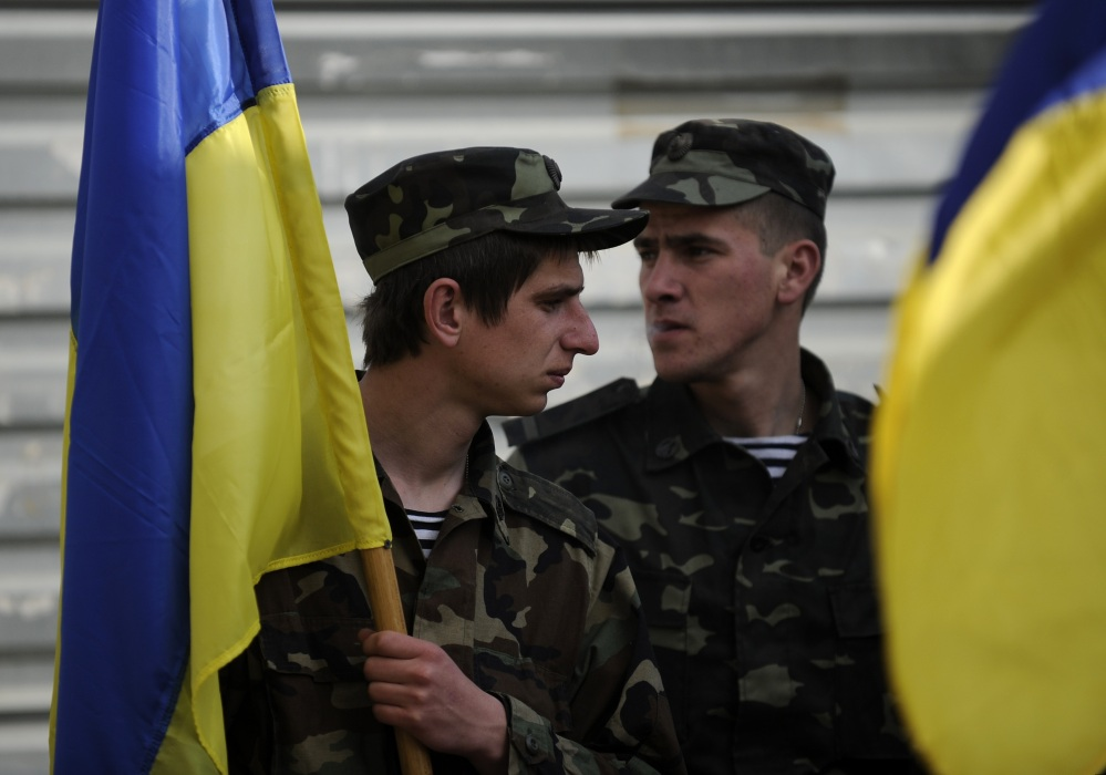 Ukrainian servicemen hold Ukrainian flags as they load their equipment into a truck in readiness to withdraw from the Belbek airbase near Sevastopol, Crimea, on Friday.