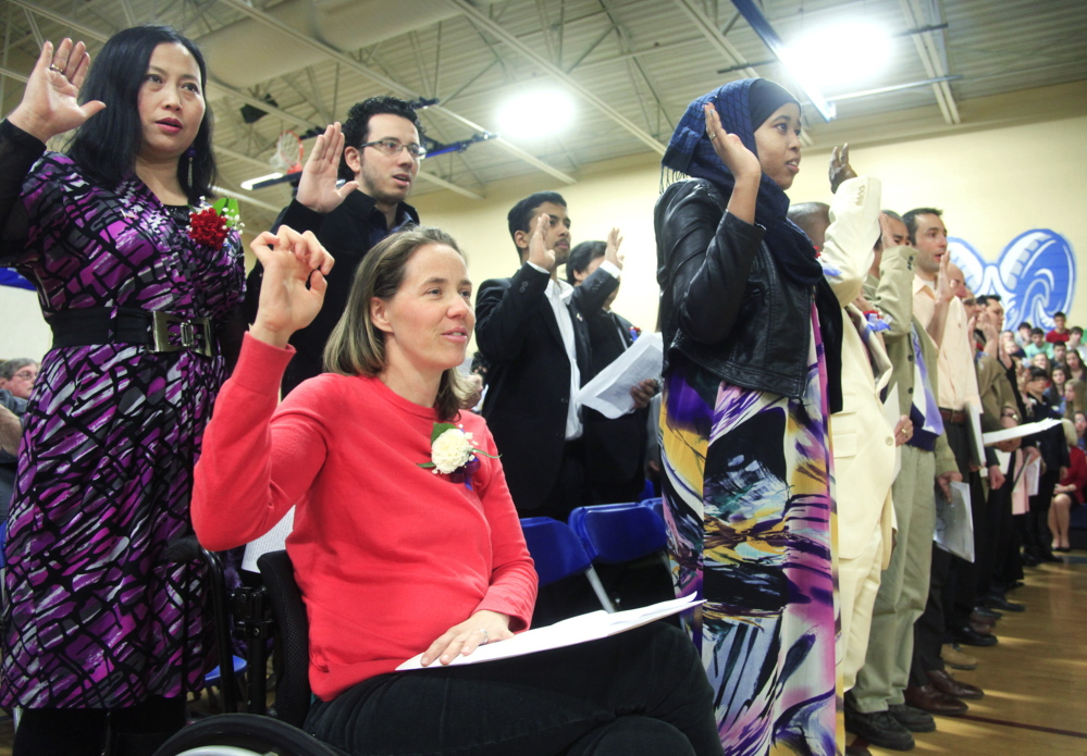 Beigette Gill of Harrison, in red, originally from Australia, joins other candidates for citizenship as they take the Oath of Allegiance during the U.S. Citizenship and Immigration Services naturalization ceremony at the Middle School of the Kennebunks in Kennebunk on Friday.