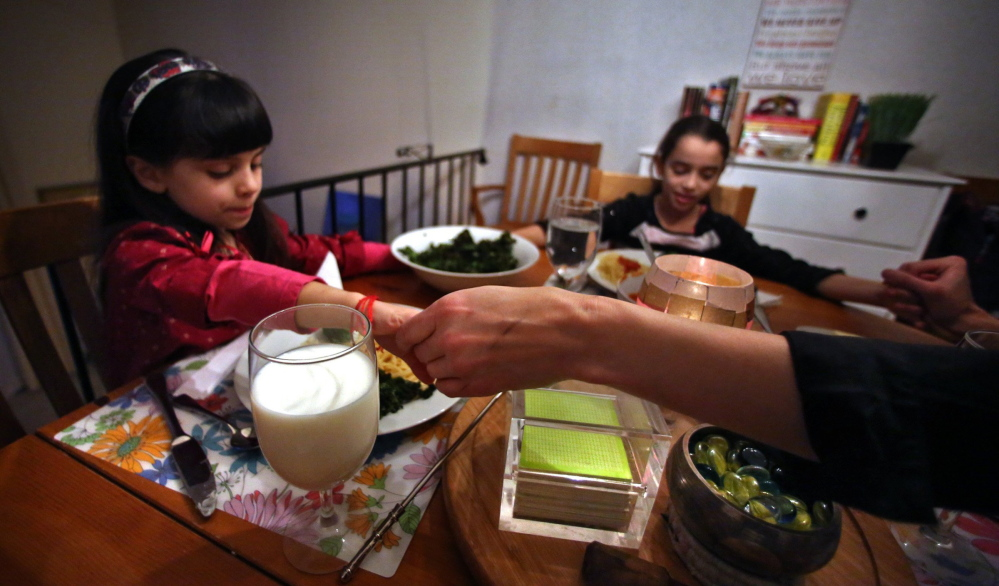 St. Paul, Minn., resident Amy Bryant, right, gives thanks before enjoying a recent evening meal with her daughters Sophie, 5, who is