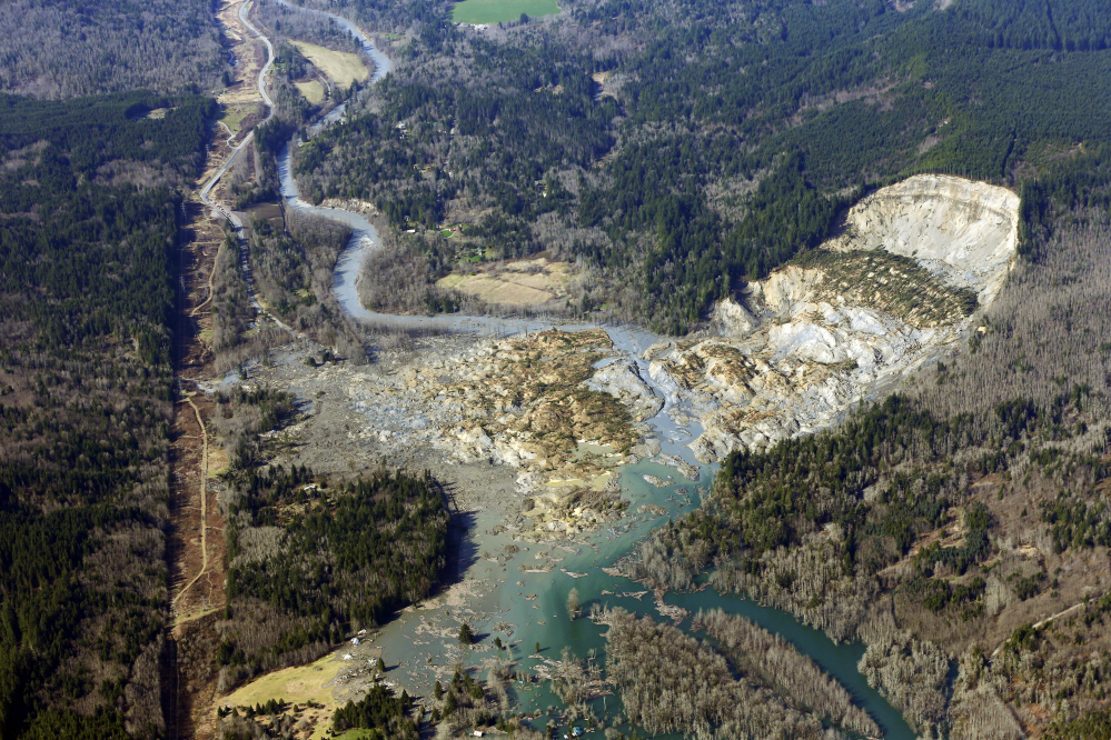This aerial photo shows the massive mudslide that killed at least eight people Saturday and left dozens missing, near Arlington, Wash.