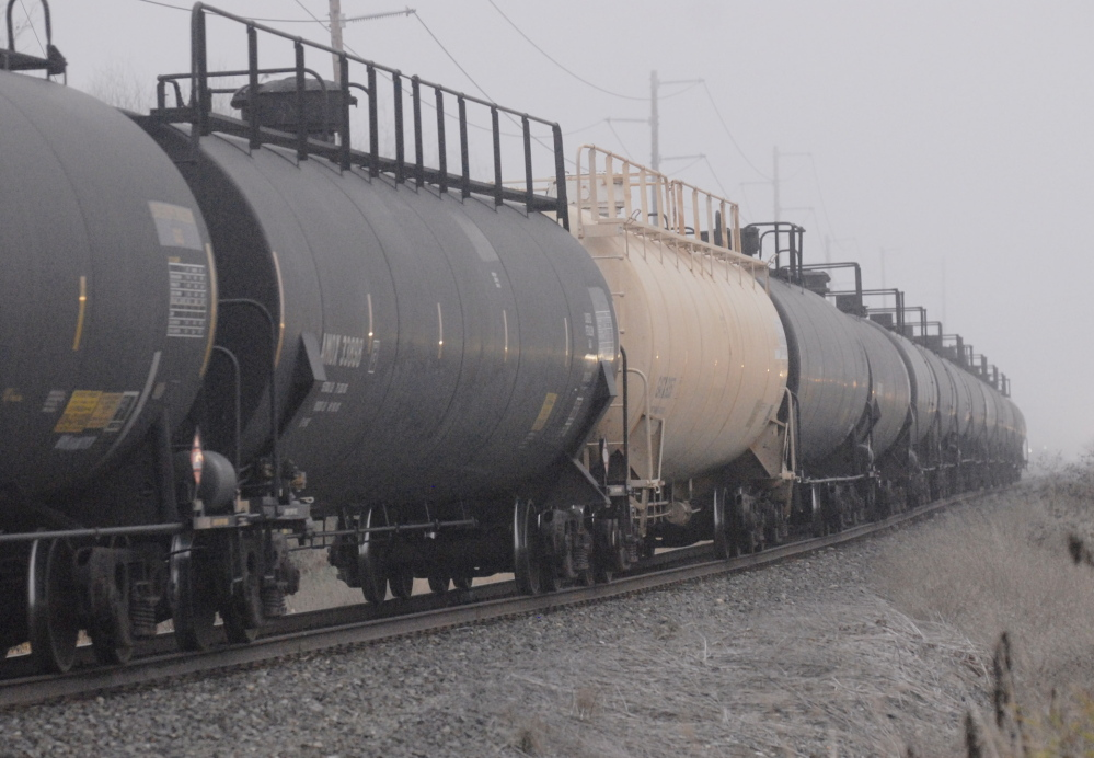 Black tank cars of the type used to transport crude oil from North Dakota head toward a refinery in Anacortes, Wash. Federal regulators say the industry hasn't provided data requested months ago.