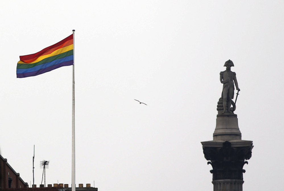 The rainbow flag, a symbol of lesbian, gay, bisexual, and transgender community, flies over a building next to Nelson's Column in Trafalgar Square in London on Friday to mark the start of same-sex weddings in the UK on Saturday.