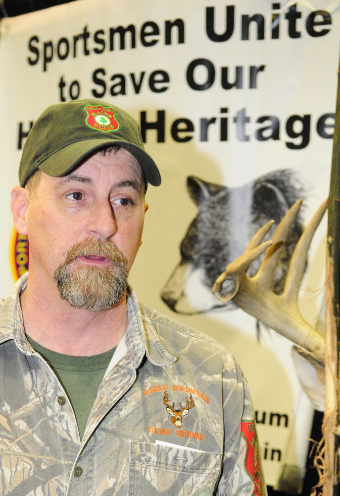 Bear hunting guide Matt Whitegiver answers a question about the pending bear hunt referendum Saturday at the State of Maine Sportsman's Show in the Augusta Civic Center.