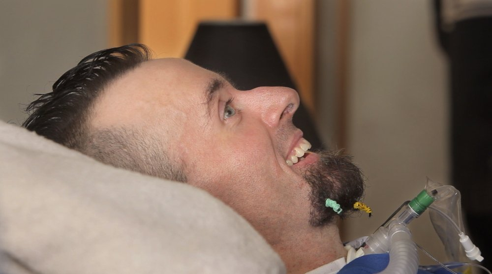 Nick Stanley smiles as he listens to the rapper Spose perform. Stanley is confined to bed because of complications from adult onset spinal muscular atrophy.