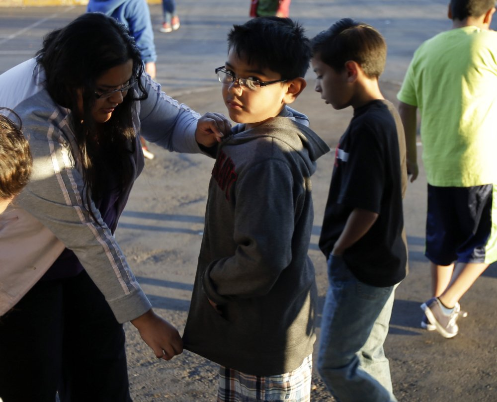 Marina Beltran zips up the jacket of her son Antonio before he takes part in the running program.