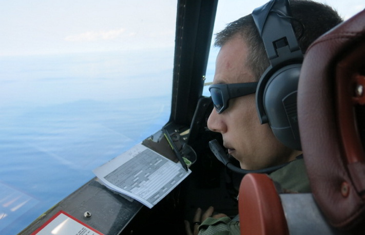 Lt. Chris Kovach peers out the window of a U.S. Navy P3 Orion surveillance aircraft flying over the Indian Ocean west of Indonesia on March 24. The constant scanning messes with your mind, he said.