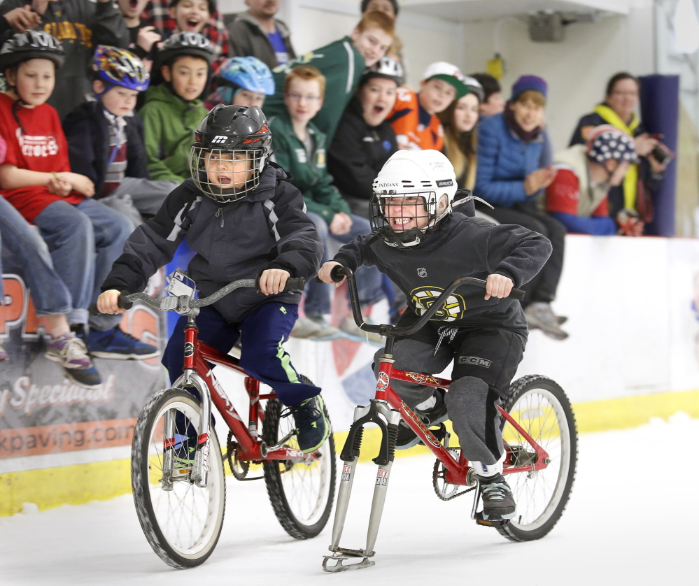 Cameron Bourgue, left, edges out Maverick White, both 7 years old and from Biddeford, on Sunday during a bike race on ice at the Biddeford Ice Arena to benefit the Community Bicycle Center.