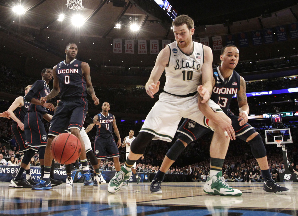 Michigan State's Matt Costello, center, looks for the ball while covered by Connecticut's Shabazz Napier, right, in the first half of a regional final at the NCAA college basketball tournament on Sunday.