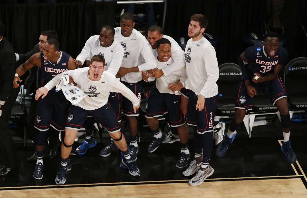 Connecticut players react during the second half in a regional semifinal at the NCAA college basketball tournament against the Michigan State, Sunday, in New York.