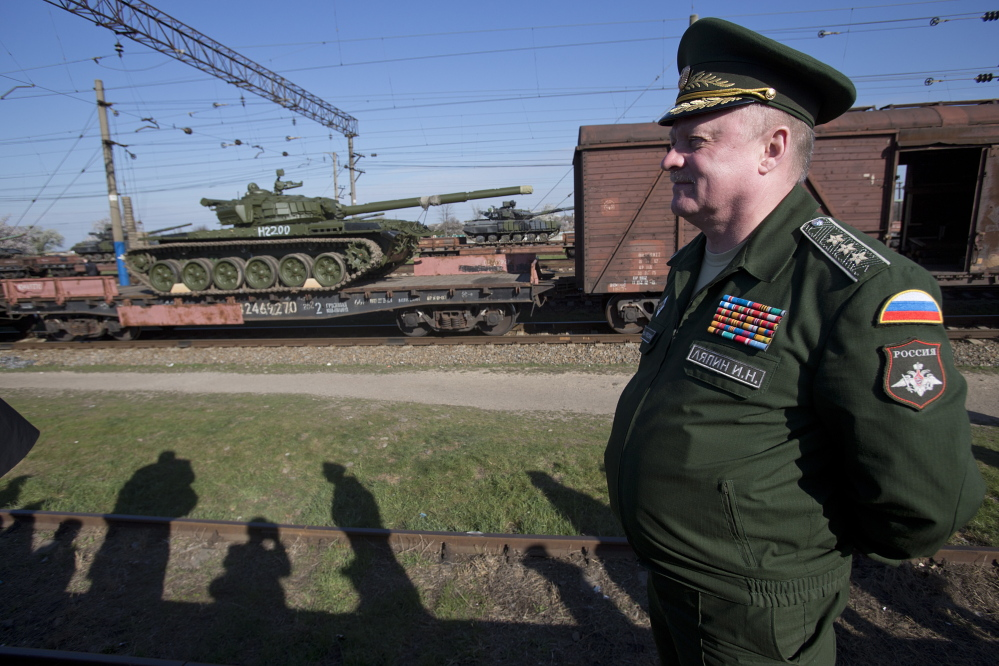 Russian Gen. Igor Lyapin watches Russian tanks, close left, arrive as Ukrainian tanks, center back, are transported to the Ukraine at a railway station in Crimea on Monday.