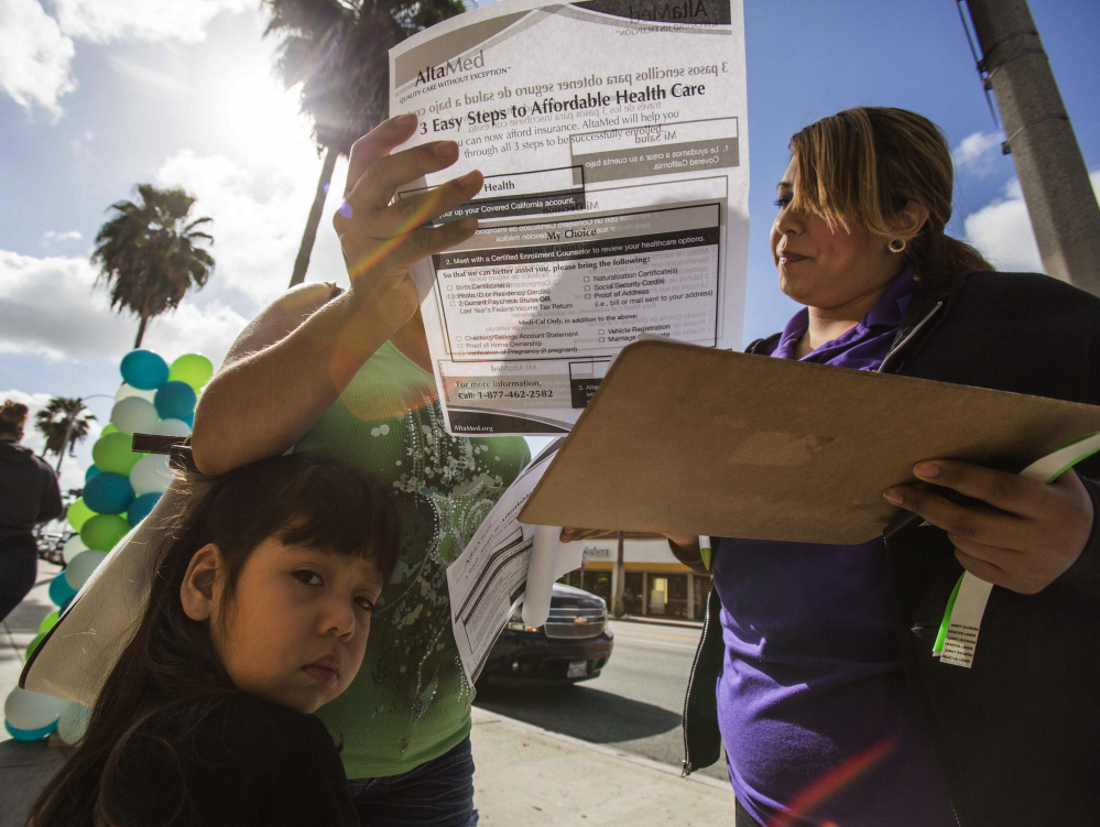Staffer Jessica Figueroa, right, assists Maria Banajas, 40, and her daughter Camila, 3, during a health care enrollment event at AltaMed Health Insurance Resource Center on Monday in Los Angeles. Monday is the open enrollment deadline for signing up for insurance under the federal Affordable Care Act.