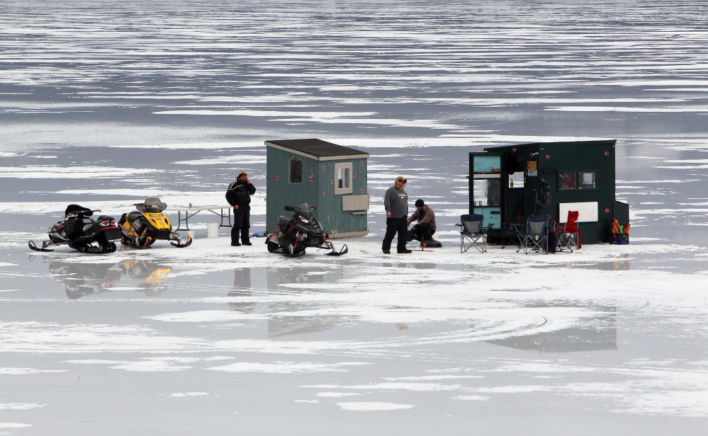 Ice fishermen are seen in Alton Bay on New Hampshire's Lake Winnipesaukee on Friday in Alton, N.H. Ice on the lake is still more than 2 feet thick in spots as the open-water season begins Tuesday.