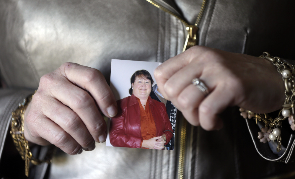 Heather Britton holds a photo of herself taken before her weight-loss surgery, at her home in Bay Village, Ohio.