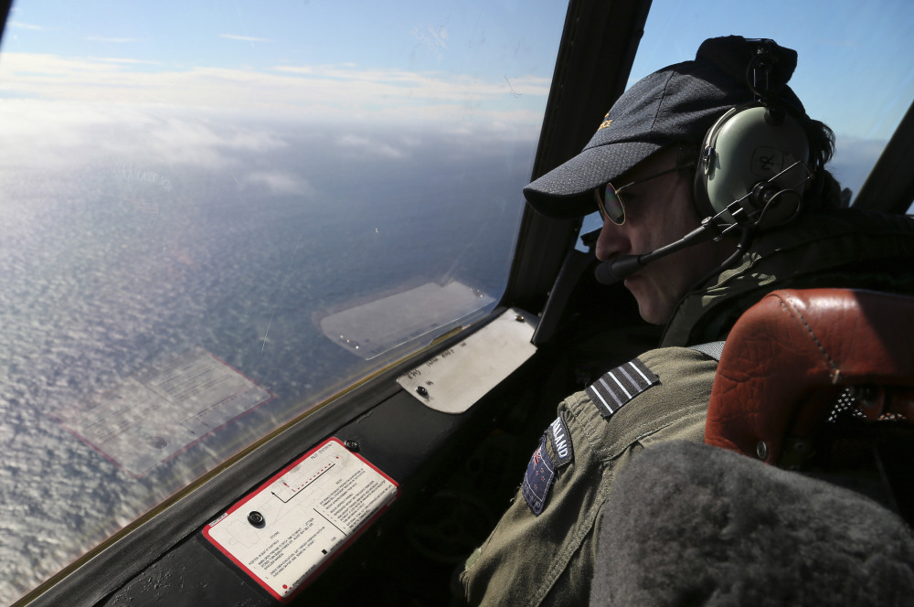 Royal New Zealand Air Force P-3 Orion's captain, Wing Comdr. Rob Shearer watches out of the window of his aircraft while searching for the missing Malaysia Airlines Flight MH370 in the southern Indian Ocean, Monday, March 31, 2014.