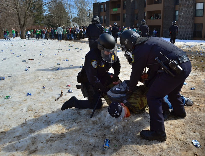 """Police detain a participant in the pre-St. Patrick's Day """"Blarney Blowout"""" near the University of Massachusetts in Amherst on Saturday."""