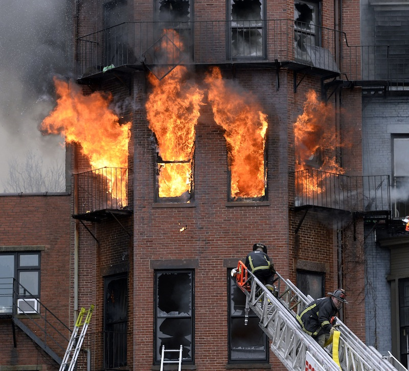 Boston firefighters work a fire on Beacon Street on Wednesday, March 26, 2014.