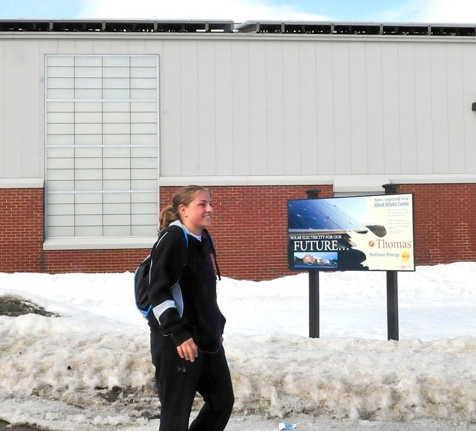 Thomas College student Scarlett Stevens walks past a sign about the solar energy that comes from the panels covering the Alfond Athletic Center at the Waterville campus March 10. Central Maine Power has informed customers that produce their own energy that rates will increase on power supplied by the electricity company.