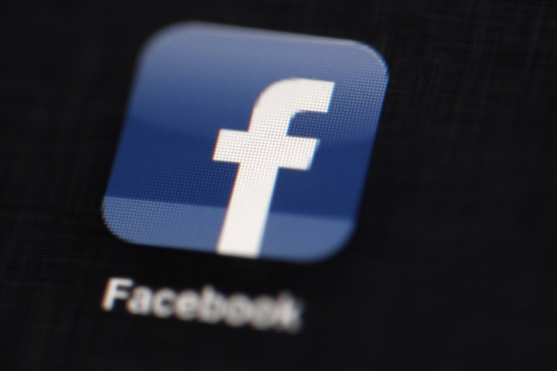 The Facebook logo is displayed on an iPad. Under pressure from gun control advocates, Facebook agreed Wednesday to delete posts from users selling illegal guns or offering weapons for sale without background checks.