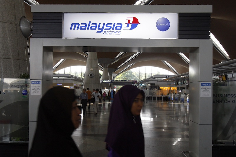 Passengers walk past a signboard of Malaysia Airlines at Kuala Lumpur International Airport in Sepang, Malaysia, on Saturday. International aviation authorities were trying to trace a Malaysia Airlines jetliner carrying 239 people that lost contact with air traffic control on its way from Kuala Lumpur to Beijing.