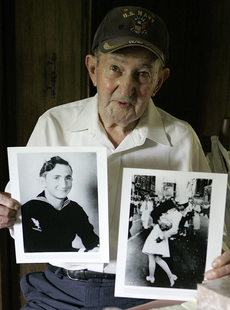 In this July 31, 2007 file photo, Glenn McDuffie holds a portrait of himself as a young man, left, and a copy of Alfred Eisenstaedt's iconic Life magazine shot of a sailor, who McDuffie claims is him, embracing a nurse in a white uniform in New York's Times Square, at his Houston home. McDuffie, who became known for claiming he was the sailor kissing a woman in Times Square in a famous World War II-era photo taken by a Life magazine photographer has died. Houston Police Department forensic artist Lois Gibson, who says she identified McDuffie as the man in the picture, says Friday, March 14, 2014 that he died March 9. McDuffie was 86.