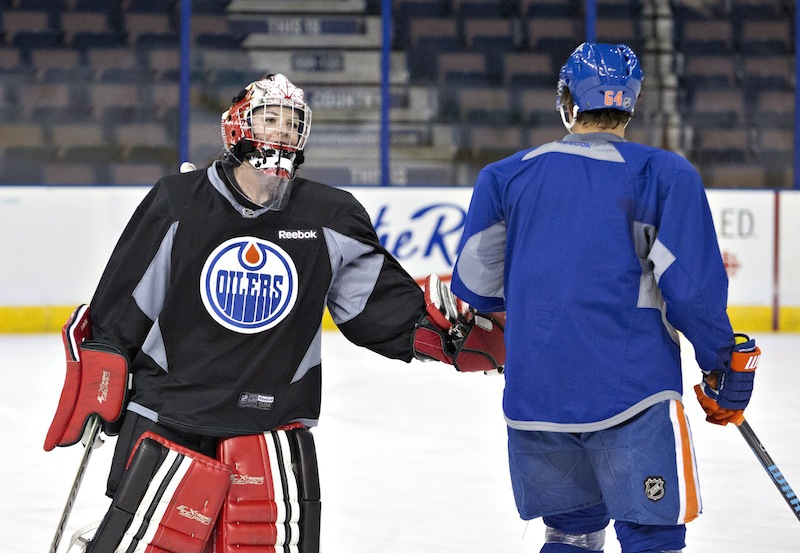 Canadian Olympic women's team goalie Shannon Szabados gives a low-five to Nail Yakupov during practice with the Edmonton Oilers NHL hockey team Wednesday.