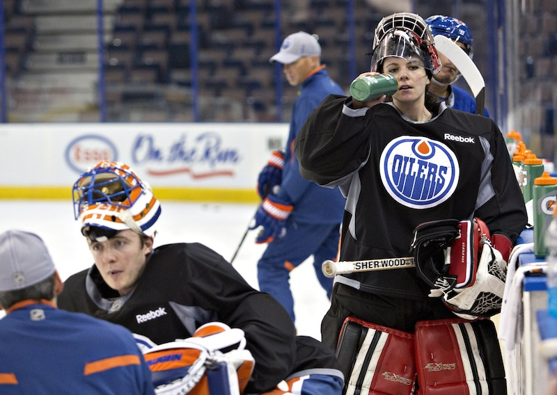 Canadian Olympic women's team goalie Shannon Szabados takes a water break during practice with the Edmonton Oilers NHL hockey team Wednesday. Oilers goaltender Ben Scrivens is at left facing the camera.