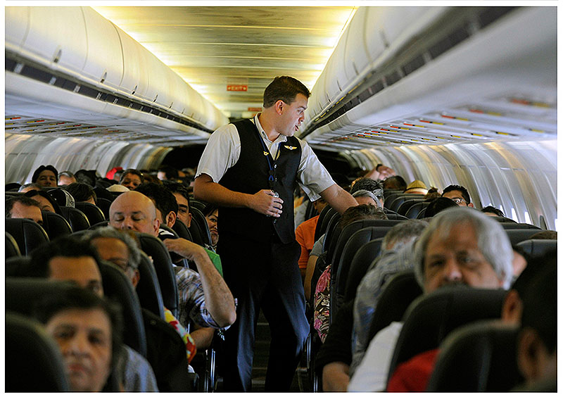 Allegiant Air flight attendant Chris Killian settles his passengers in coach class before their aircraft pushes back from the terminal at McCarran International Airport in Las Vegas.