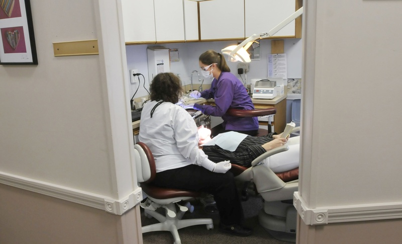 "In this November 2012 file photo, Dr. Denise Theriault and hygienist Stephanie Fortier work on a patient at Dustan Dental Center. A new type of dental provider – ""mid-level dental therapist"" – is likely on its way to becoming a reality in Maine."