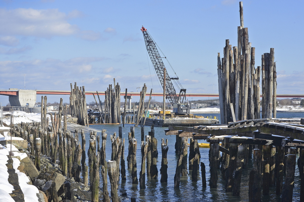 Pilings stand in the water off land in Portland owned by Phineas Sprague Jr. State officials plan to use the power of eminent domain to take most of his 22 acres, and Sprague plans to use his profit from the sale to buy nearby land for the boatyard and offices he's building.