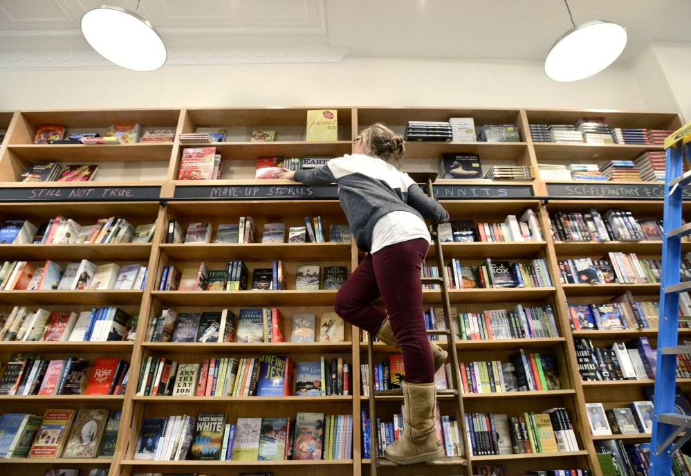 Buyer Tori Curtis stocks shelves Monday at Sherman's Books and Stationery, which will open Tuesday on Exchange Street in Portland.