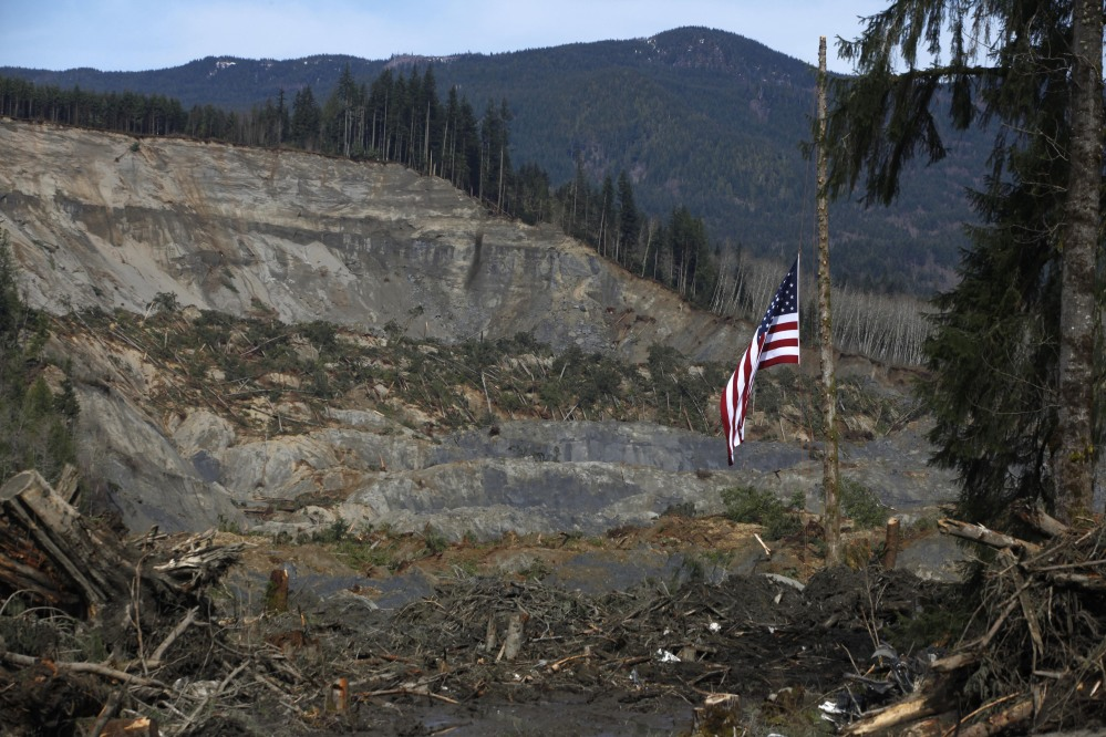 An American flag flies as half-staff Monday from the only cedar post left standing at the scene of a deadly mudslide that destroyed Oso, Wash., leaving at least 24 dead. The debris field is 70 feet deep in places.