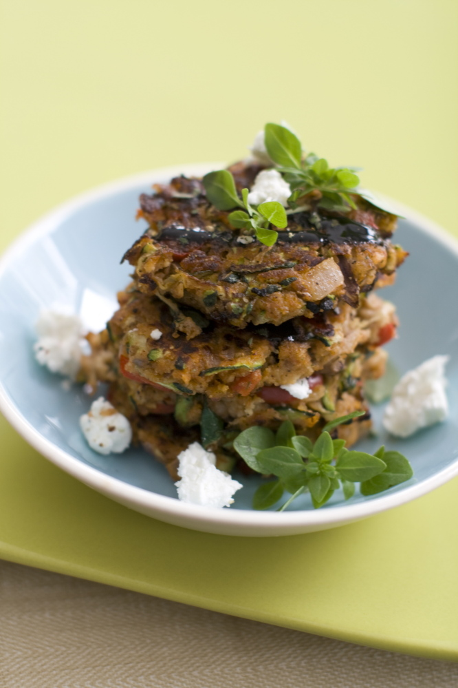 Vegetable patties made with the main ingredients of ratatouille are finished with fresh oregano, feta cheese and a drizzle of balsamic glaze.