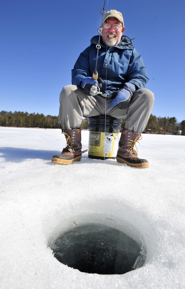 Peter Brawn of Cape Elizabeth fishes in a hole cut about 18 inches deep on Sebago Lake Tuesday.