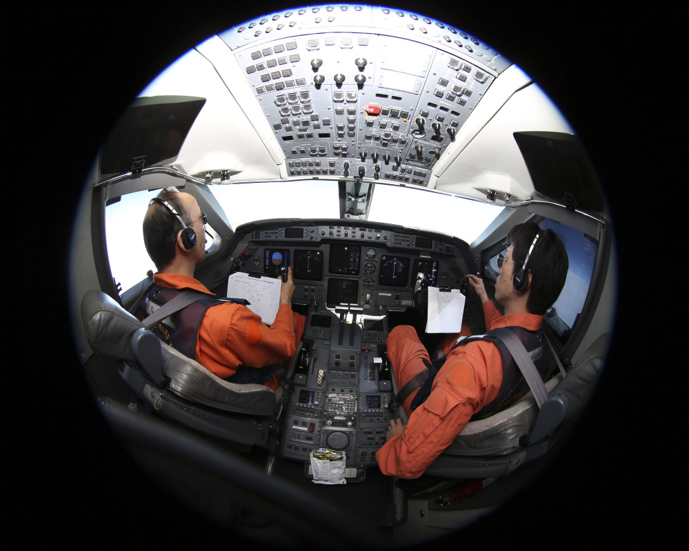 Makoto Hoshi, left, captain of the Japan Coast Guard Gulfstream, and his co-pilot Shunichi Yumiza search on Tuesday for the missing Malaysia Airlines plane.
