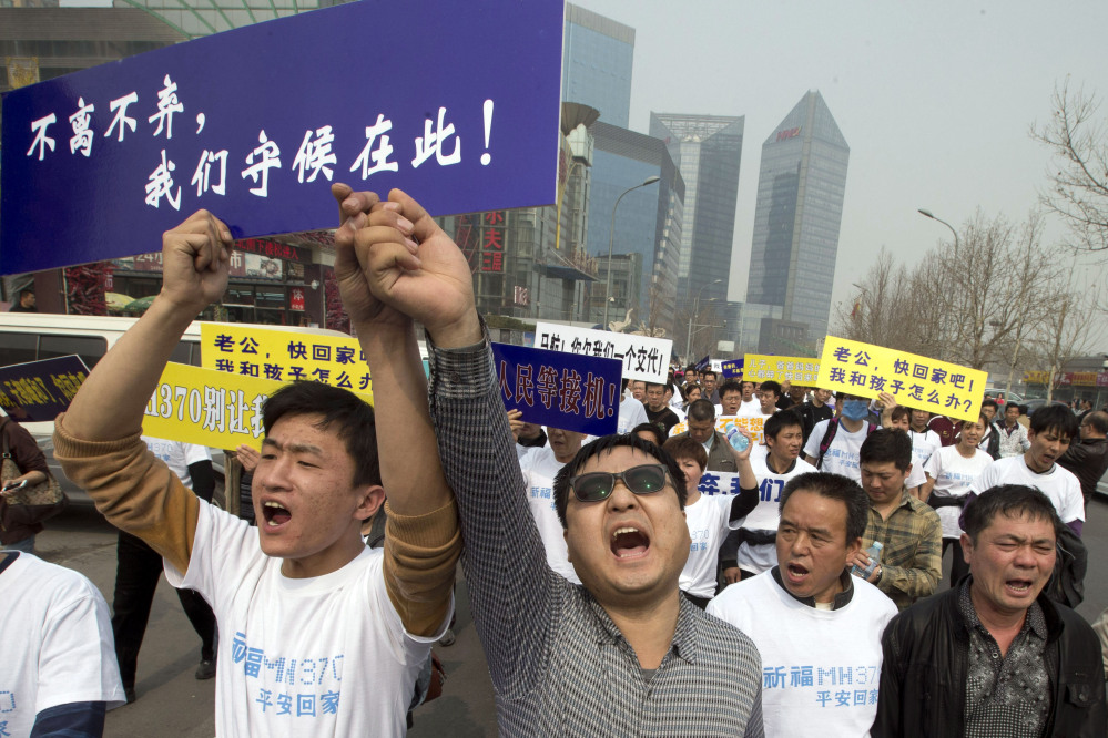"""In this Tuesday, March 25 file photo, Chinese relatives of passengers onboard the missing Malaysia Airlines plane, flight MH370, shout in protest as they march towards the Malaysia embassy in Beijing, China. Authorities have been forced on the defensive by the criticism, the most forceful of which has come from a group of Chinese relatives who accuse them of lying about - or even involvement in - the disappearance of Flight 370. The blue placard reads: """"We won't leave or ditch you, we will wait right here."""""""