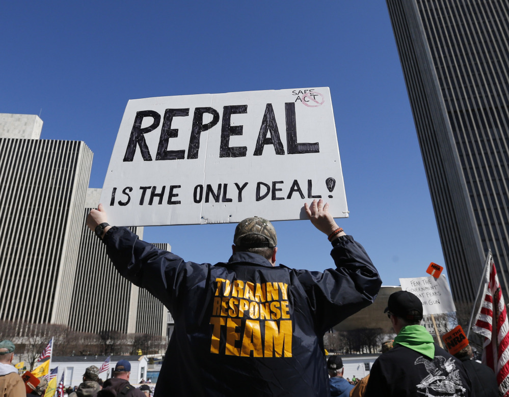 A gun rights activist holds a sign during a rally Tuesday at the Empire State Plaza in Albany, N.Y. Activists are seeking a repeal of a 2013 state law that outlawed the sales of some popular guns like the AR-15.