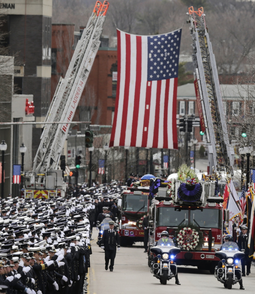 The funeral procession for Lt. Edward Walsh rolls under a flag spanning Main Street en route to St. Patrick's Church in Watertown, Mass., Wednesday. Walsh and colleague Michael Kennedy died while battling a nine-alarm blaze in Boston's Back Bay.